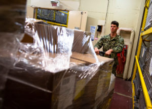 Caption: Logistics Specialist Seaman Allan Teschner, from Northport, Fla., receives medical supplies aboard the hospital ship USNS Mercy (T-AH 19), March 29, 2020. (U.S. Navy photo by Mass Communication Specialist 2nd Class Ryan M. Breeden/Released)
